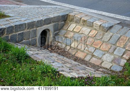 Sewer Bridge Through A Ditch By The Road. Concrete Hole With Surroundings Of Stone Paving. Grassy Sl