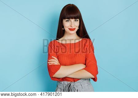 Pretty Young Red Haired Woman With Bright Red Lipstick, Wearing Red Shirt And Gray Pants, Posing Wit