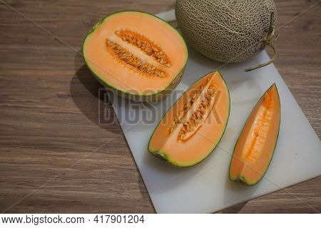 Cut Three Orange Cantaloupe And Cantaloupe On A White Plastic Chopping Board On A Wooden Floor Backg