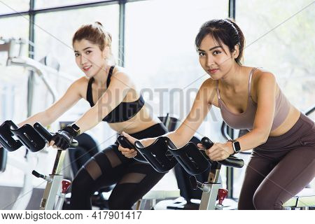 Asian Young Woman Beautiful People Talking And Smiling While Working Out On Bike At Fitness Gym. The
