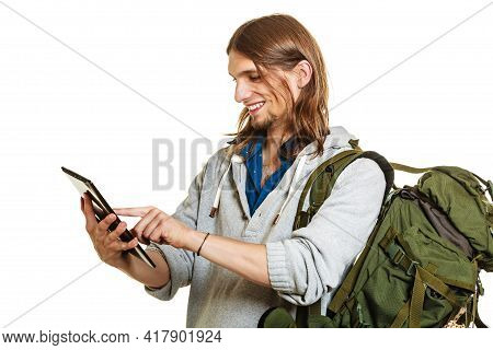 Backpacker Man Using Pc Computer Tablet Browsing Surfing The Internet. Young Hiker Backpacking. Mode