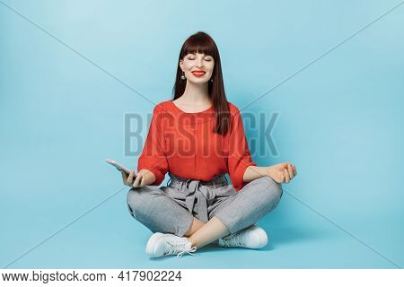 People, Technologies Concept. Relaxed Smiling Young Woman, Wearing Red Shirt And Gray Pants, Meditat