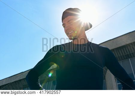 Bottom View Of An Athlete In Sportswear With Hands On The Waist Posing On A Sunlight. Portrait Of An
