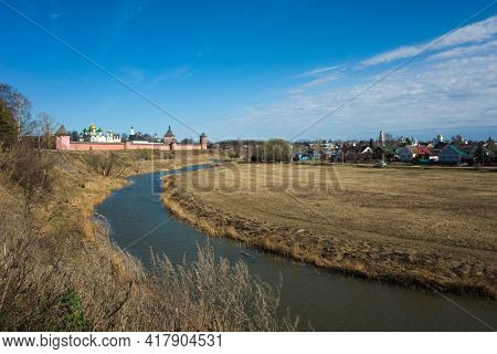 Suzdal view with river Kamenka, Saint Euthymius monastery red wall with towers, residential area and central Russia nature in spring in middle april, Golden Ring of Russia