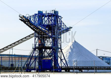 Salt Mountains Next To Machinery Of Salt Plant Under Blue Sky In Santa Pola, Spain