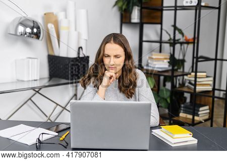 Concentrated Woman Is Staring At The Laptop Screen Sitting In The Office, Thoughtful Focused Female