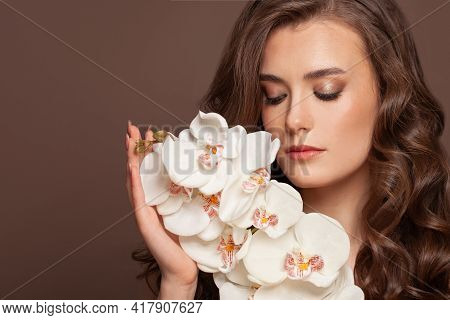 Attractive Young Woman Face With Healthy Clear Skin And White Orchid Flowers. Facial Treatment And S