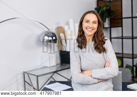 Cheerful Woman Entrepreneur Stands With Arms Crossed In The Contemporary Home Office, Cheerful Freel