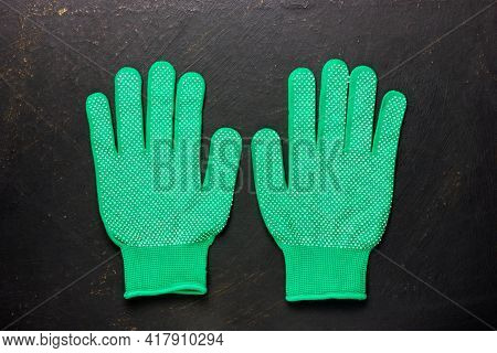 Two Green Work Gloves On A Black Background. Gardening Gloves. A Pair Of Gloves.