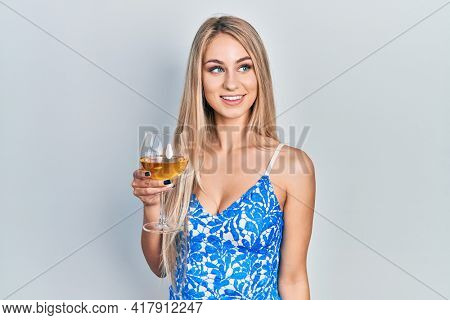 Young beautiful caucasian woman drinking a glass of white wine smiling looking to the side and staring away thinking.