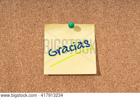Thanks Word In Spanish Language On Yellow Note On Cork Board