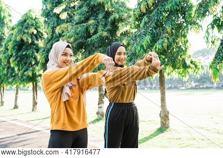 Two Veiled Muslim Girls Stretch Their Hands Before Jogging And Outdoor Sports
