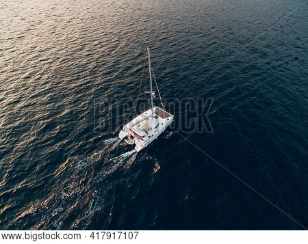 White Sailing Catamaran Yacht Sails In The Blue Sea