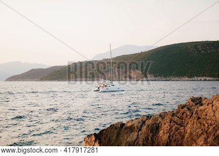 White Sailing Yacht Sails On The Sea Past The Mountainous Coast