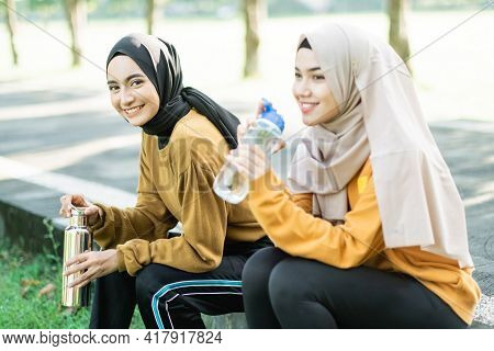 Two Veiled Girls Sitting Enjoy Drinking Water With Bottle After Doing Outdoor Sports Together
