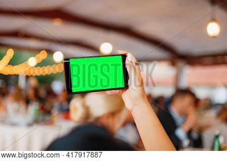 Womans Hand With A Smartphone Photographs The Party. Blank Screen