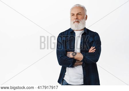 Cool Senior Man With Tattoos, Bearded Granfather Cross Arms On Chest, Looking Aside With Serious Coo