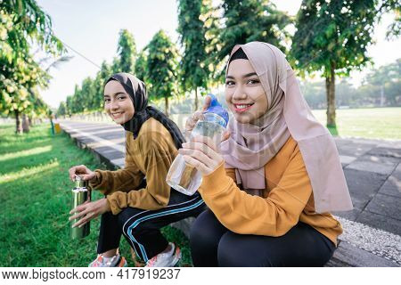 Smiling Two Asian Muslim Girls Drinking Water Using Bottles After Sports Together In The Afternoon
