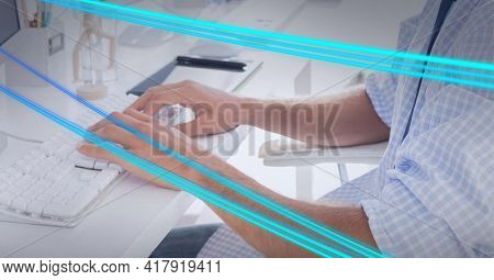 Composition of blue light trails over man using computer in office. global technology and digital interface concept digitally generated image.