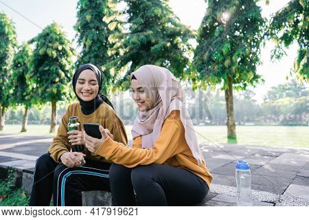 Smiling Two Asian Muslim Girls Using A Handphone Together When Holding A Bottles After Sports Togeth