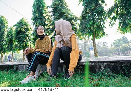 Two Girls Wearing Hijab Smiling And Enjoy The Afternoon After Exercising Together