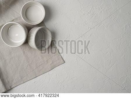 Flat Lay Of Three Empty White Ceramic Ramekins Stacked Against White Background, Served Linen Napkin