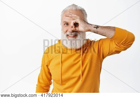 Happy Old Man With Tattoos Showing Okay Sign, Looking Through Ok Fingers And Smiling Pleased, Satisf