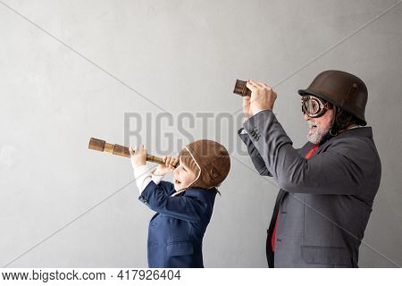 Funny Child And Senior Man Pretend To Be Businessmen. Grandfather And Kid Playing At Home. Education
