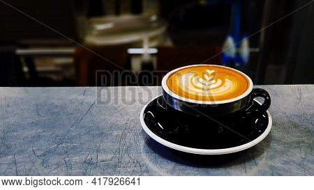 Latte Art Cappuccino Coffee Of Black Cup Putting On Stainless Steel Table With Dark Or Black Backgro