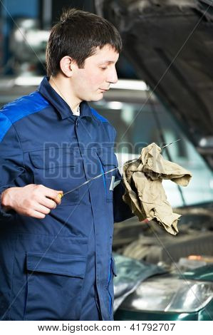 auto mechanic technician examining level during replacing and pouring motor oil into automobile engine at maintenance repair service station