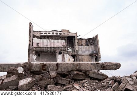 A Destroyed Building Against A Gray Sky With A Pile Of Concrete Rubble In The Foreground. Background