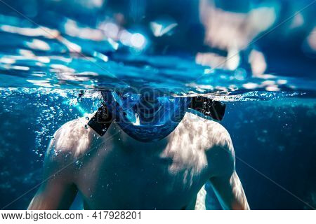 Man in snorkeling mask underwater swimming