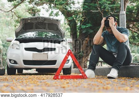 Asian Man Using Smartphone For Assistance After A Car Breakdown On Street. Concept Of Vehicle Engine