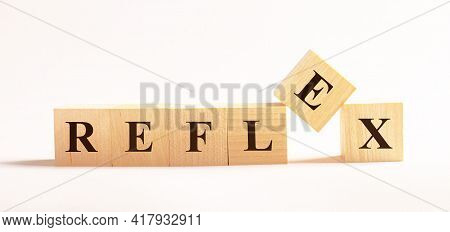 On A Light Background, Wooden Cubes With The Text Reflex