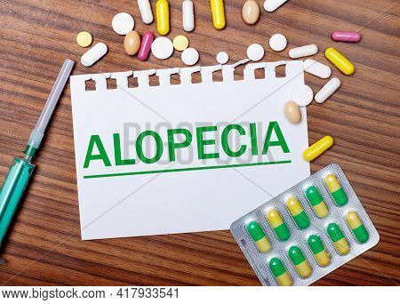 On A Wooden Table, A Syringe, Pills And A Sheet Of Paper With The Inscription Alopecia. Medical Conc