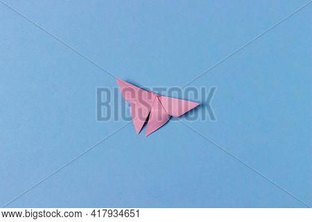 Pink Origami Butterfly Folds Out Of Paper. In Center Of A Blue Background. Education, Pastime, Hobbi