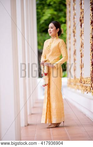 An Elegant Thai Woman In Thai Dress Adorned With Precious Jewelry Holds A Flower Garland In A Beauti