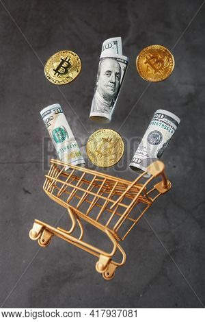 Dollar Bills And Itkon Coins Flew Out Of The Golden Basket On A Dark Background.