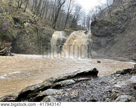 Beautiful Landscape Of Powerful Muddy Waterfall In Mountainous Terrain. Dirty Mountain Waterway Flow