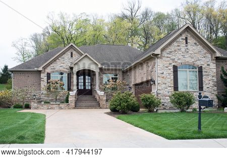 Luxurious Beige Stone and Brick Home In Springtime