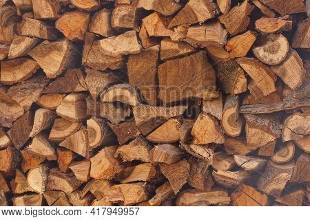 Brown Wood Texture Of Chopped Dry Firewood In The Wall