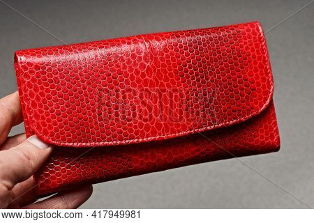 Hand Holds Closed Large Red Leather Wallet On Gray Background