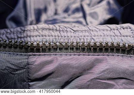 Open Zip With Black Plastic Teeth On Gray Cloth Fabric