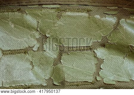 Green Fabric Texture With Pieces Of Plastic With Cracks