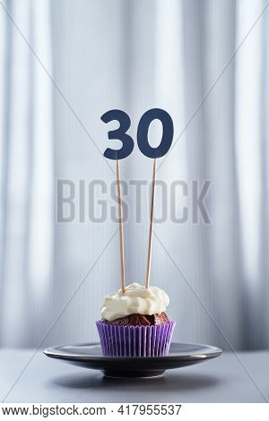 Homemade Chocolate Anniversary Cupcake With Creamy Topping And Number 30 Thirty On Black Plate And B