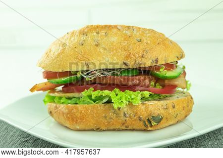 A Sandwich With Bacon And Fresh Vegetables. Appetizing Sandwich On A Light Background With Space For