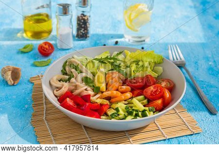 Healthy Salad With Fresh Vegetables, Shrimps And Squid In A Gray Bowl On A Light Blue Concrete Backg