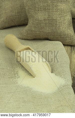 Semolina In A Wooden Spoon On A Wooden Background. Background With Space For Text