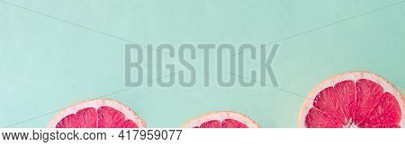 Fresh Sliced Ripe Grapefruit On Green And Pink Background, Top View. Halved Grapefruit.flat Lay Desi