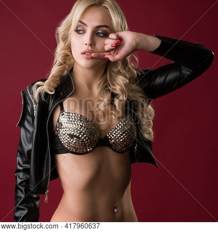 Model In Leather Jacket And Lingerie Posing On Red